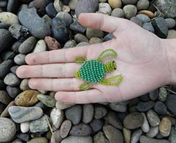 beaded turtle in palm