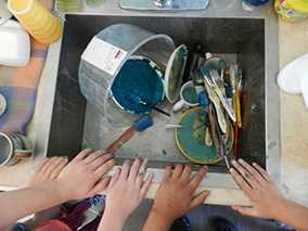 kids hands at the sink with used painting implements